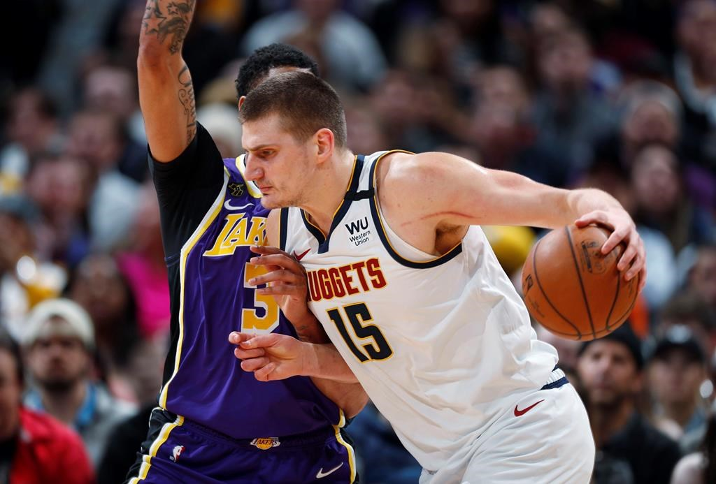 FILE - In this Feb. 12, 2020, file photo, Denver Nuggets center Nikola Jokic drives as Los Angeles Lakers forward Anthony Davis defends during the first half of an NBA basketball game in Denver. A person with knowledge of the situation says Jokic has tested positive for the coronavirus and is quarantining in his native Serbia. (AP Photo/David Zalubowski, File).