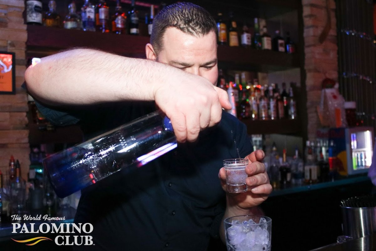 A bartender pours a drink at the Palomino Club during a recent New Year's celebration. The province won't allow patrons to dance or grab a drink up at the bar in the province's third phase of reopening.