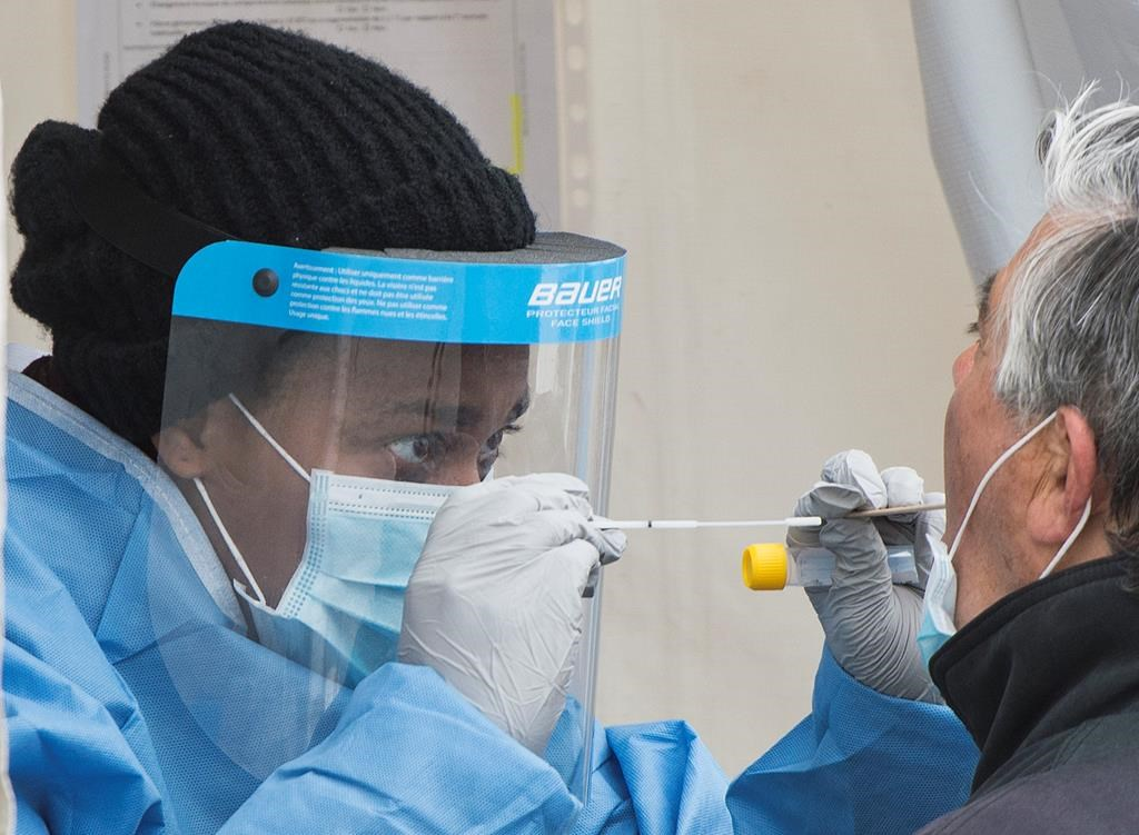 A health-care worker prepares to swab a man at a walk-in COVID-19 test clinic in Montreal on Sunday, May 10, 2020.