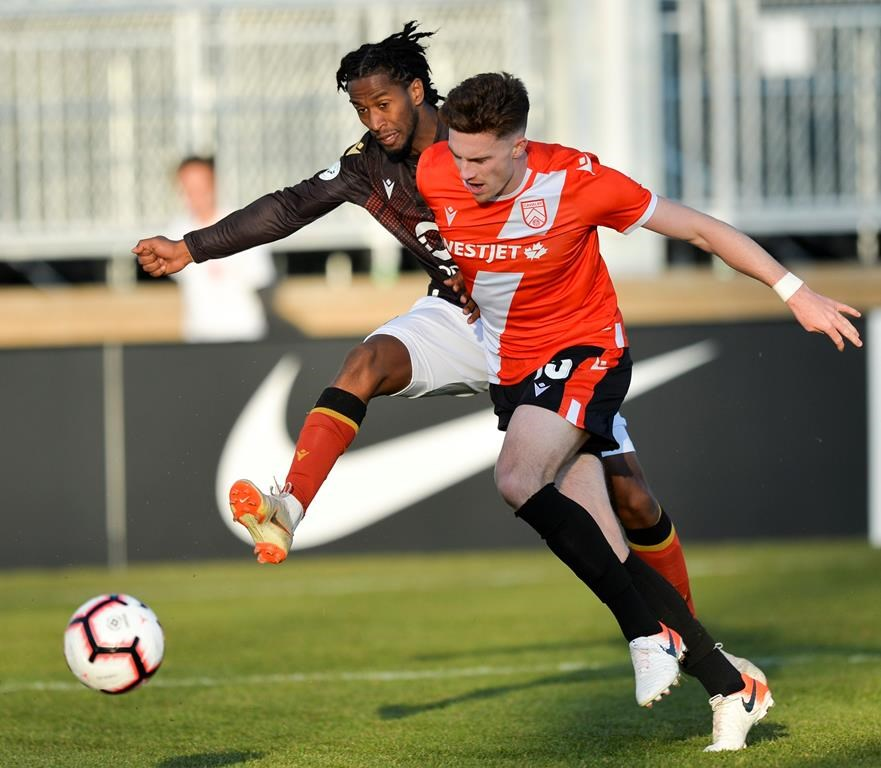 Ali Musse of Valour FC (left) and Joel Waterman of Cavalry FC vie for the ball during CPL action in Calgary, May 8, 2019. It looks like Prince Edward Island will lead the way in Canada's return to soccer, with the Canadian Premier League possibly looking to finally kick off its season in Charlottetown. THE CANADIAN PRESS/HO-CPL-Mike Sturk MANDATORY CREDIT.