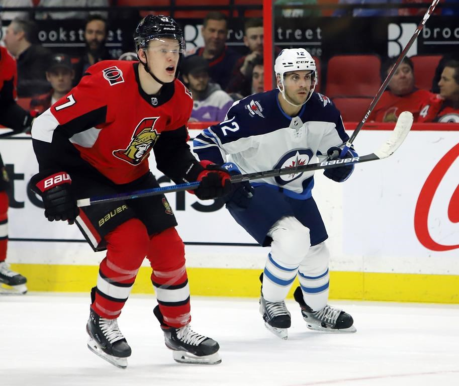 Winnipeg Jets defenceman Dylan DeMelo (12) and Ottawa Senators left-winger Brady Tkachuk (7) look down ice towards the play during second-period NHL action in Ottawa on Thursday, Feb. 20, 2020.