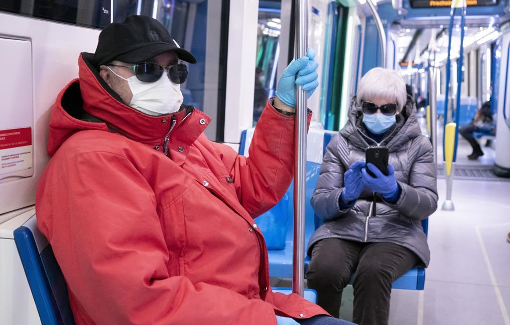 A couple wearing protective masks ride a near-empty subway train in Montreal on Wednesday, April 22, 2020.