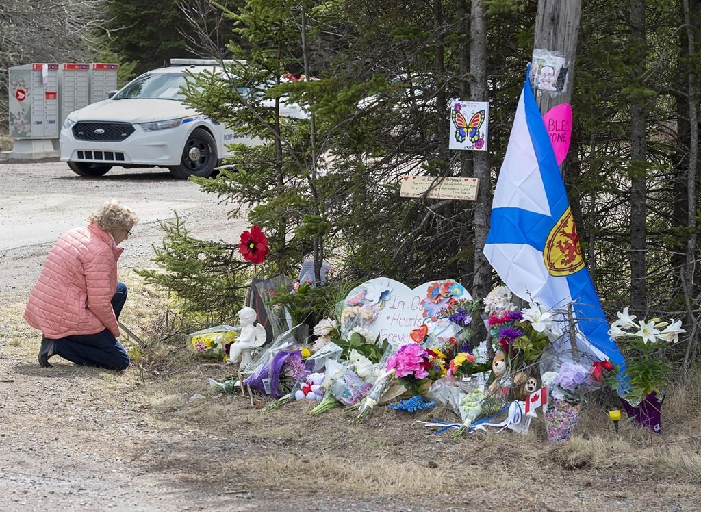 A woman pays her respects to victims of a mass shooting at a roadblock in Portapique, N.S., on Wednesday, April 22, 2020. More than seven weeks after a man disguised as a Mountie killed 22 people in rural Nova Scotia, the RCMP have finally hinted at what may have motivated one of the worst mass killings in Canadian history. THE CANADIAN PRESS/Andrew Vaughan.