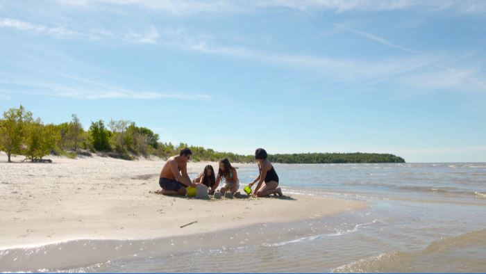 Vacationers enjoying some time in the sun at a Manitoba beach.
