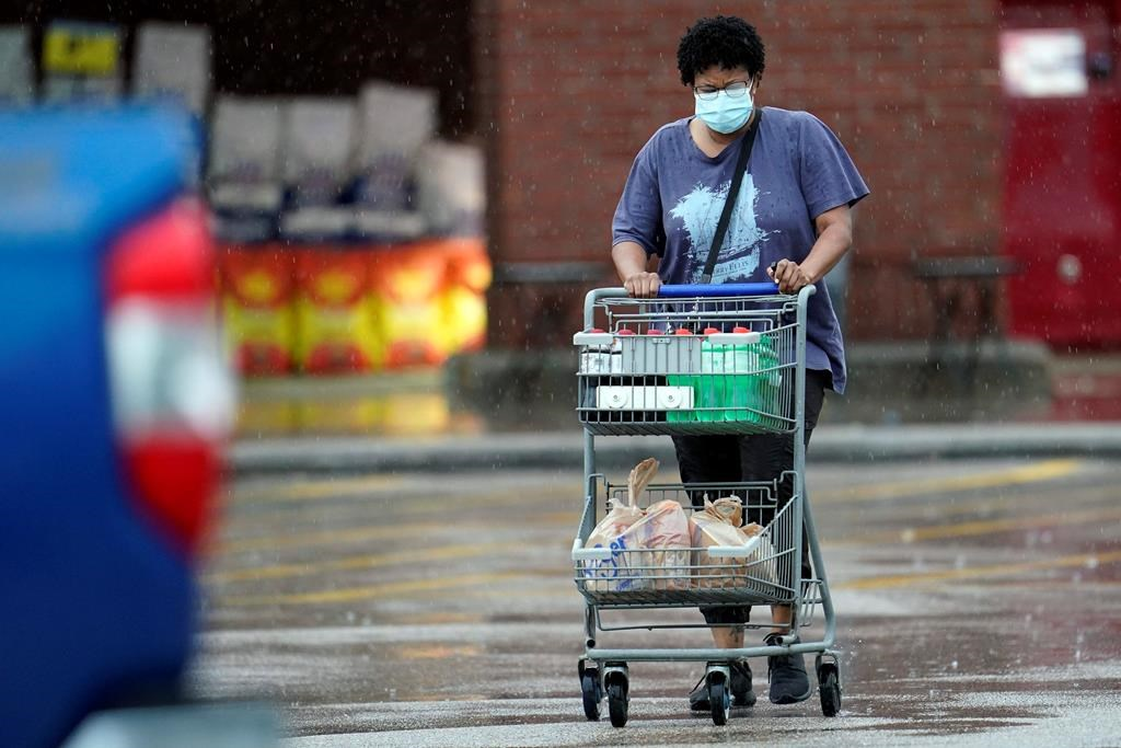 A shopper wears a mask as she pushes her grocery cart in the rain Thursday, June 25, 2020.