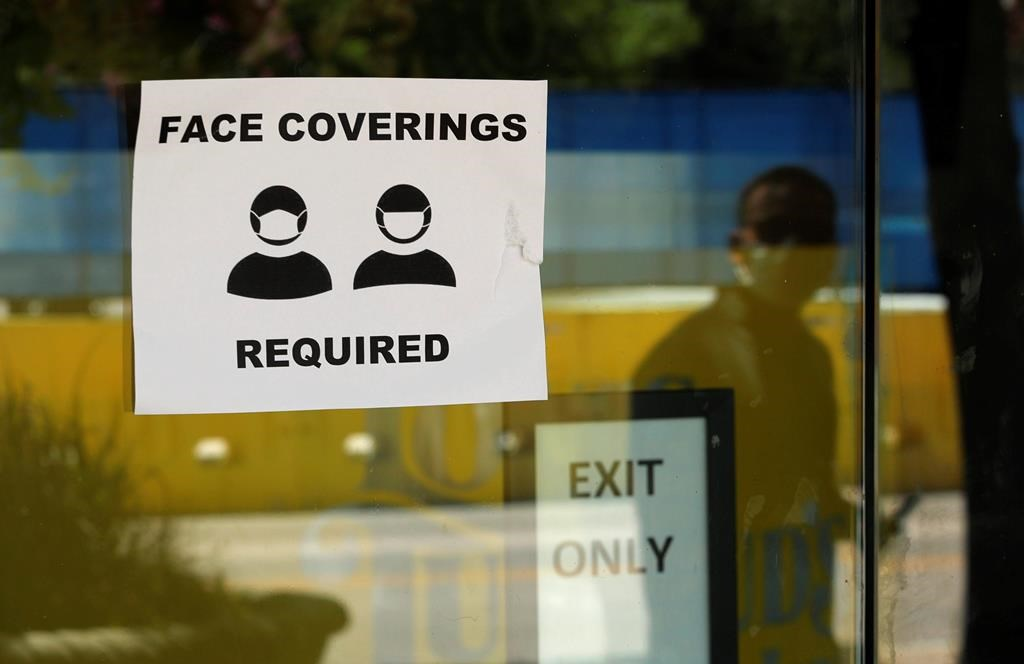A man wearing a mask to protect against the spread of COVID-19 is reflected next to a sign requiring face coverings at a business in San Antonio, Wednesday, June 24, 2020.