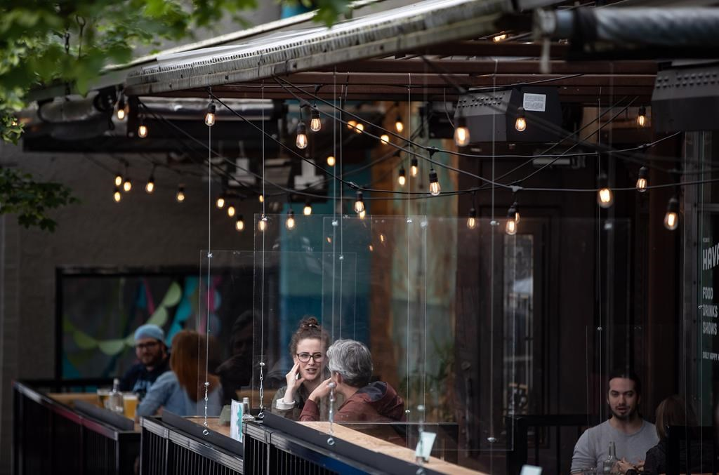 Patrons sit between plexiglass barriers on the patio of a restaurant and bar in Vancouver, on Sunday, May 31, 2020.