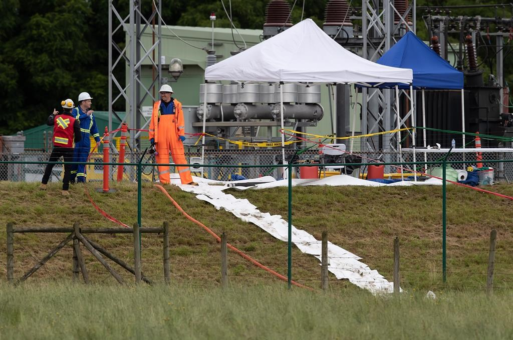 Workers are seen at the site of a crude oil spill at a Trans Mountain Pipeline pump station in Abbotsford, on Sunday, June 14, 2020.
