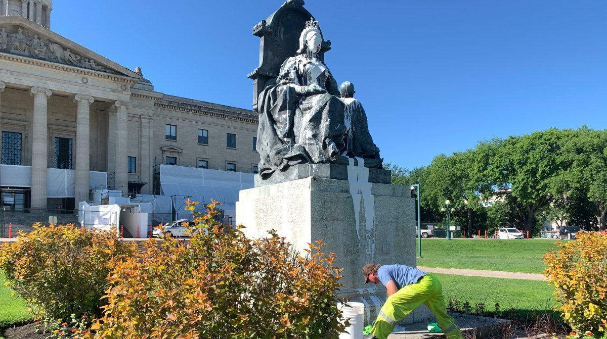 City workers clean up the statue of Queen Victoria in front of the Manitoba Legislature.