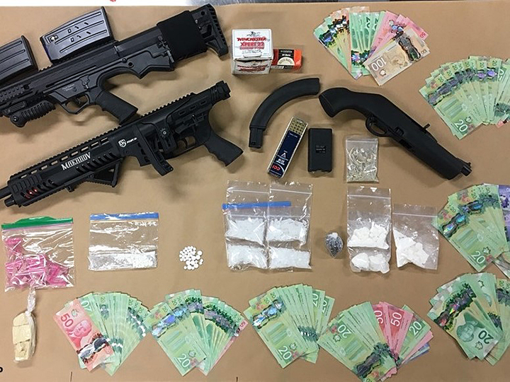 A police photo showing money, drugs and firearms that were allegedly seized during two simultaneous drug busts in West Kelowna on Tuesday.