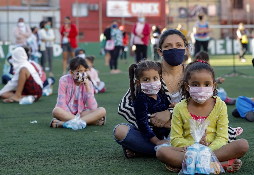Residents sit on a soccer field as they wait to receive kits equipped with cleaning products and protective face masks for children, provided by a non-governmental organization as a measure to help control the spread of the new coronavirus, in the Paraisopolis slum of Sao Paulo, Brazil, Wednesday, June 24, 2020. With over 100,000 residents, Paraisopolis is one of the areas of Sao Paulo that is most affected by COVID-19. (AP Photo/Andre Penner).