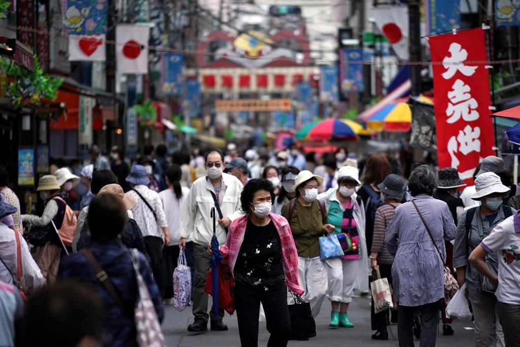 A street is crowded by shoppers in Tokyo Wednesday, June 24, 2020. Japan's economy is opening cautiously, with social-distancing restrictions amid the coronavirus pandemic.