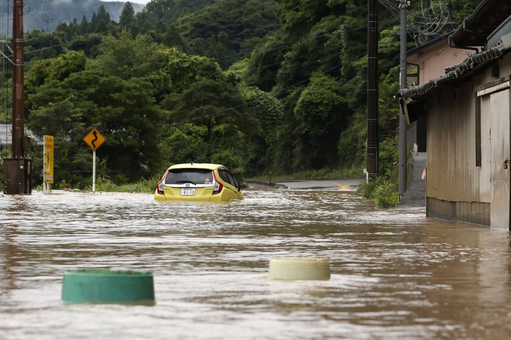 A car is stuck in a flooded road by heavy rain in Yatsushiro, Kumamoto prefecture, southwestern Japan, Saturday, July 4, 2020. The Japan Meteorological Agency raised the heavy rain warnings in many parts of the prefectures to the highest level shortly before 5 a.m. It was the first time for the agency to do so in the two prefectures, Kumamoto and Kagoshima.