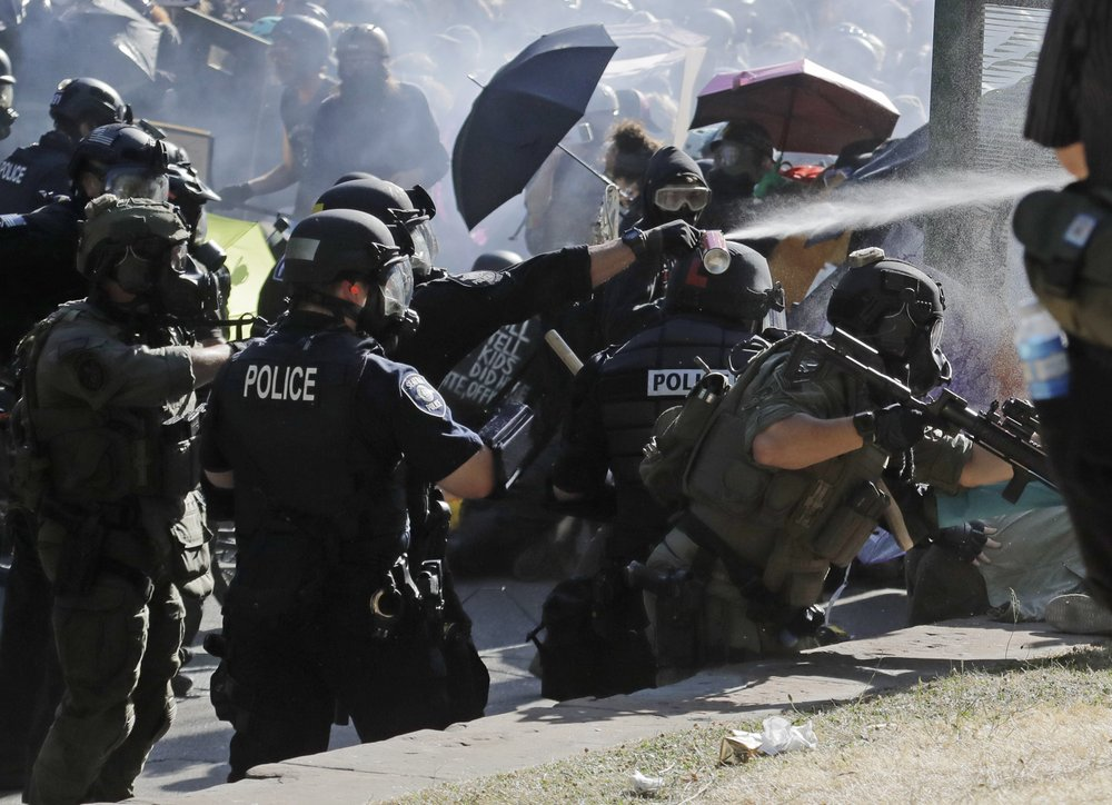 Police pepper spray protesters, Saturday, July 25, 2020, near Seattle Central Community College in Seattle. A large group of protesters were marching Saturday in Seattle in support of Black Lives Matter and against police brutality and racial injustice.