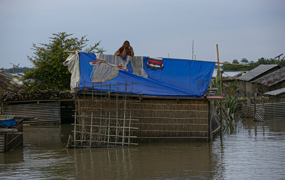 A flood affected Indian woman stands on the roof of her partially submerged house along river Brahmaputra in Morigaon district, Assam, India, Thursday, July 16, 2020. Floods and landslides triggered by heavy monsoon rains have killed dozens of people in this northeastern region.