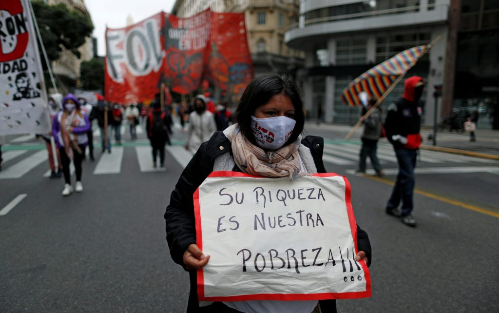 """FILE PHOTO: A demonstrator holds a placard that reads """"their richness is our poverty"""", during a protest to demand resources for the vulnerable, amid the coronavirus disease (COVID-19) lockdown, in Buenos Aires, Argentina May 21, 2020."""