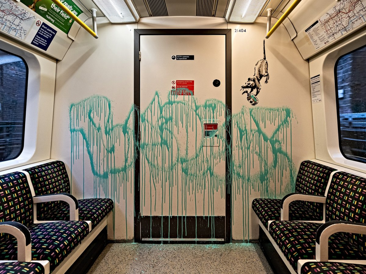 This undated photo issued on Tuesday July 14, 2020 by JBPR, shows Banksy's latest work sprayed on the inside of a London Underground tube carriage. Enigmatic graffiti artist Banksy uploaded a video to social media on Tuesday of what appeared to be him in disguise as a professional cleaner spray painting images of rats on the inside of a London Underground train along with messages about spreading the novel coronavirus.