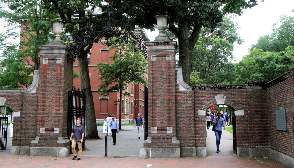 FILE - In this Aug. 13, 2019, file photo, pedestrians walk through the gates of Harvard Yard at Harvard University in Cambridge, Mass.