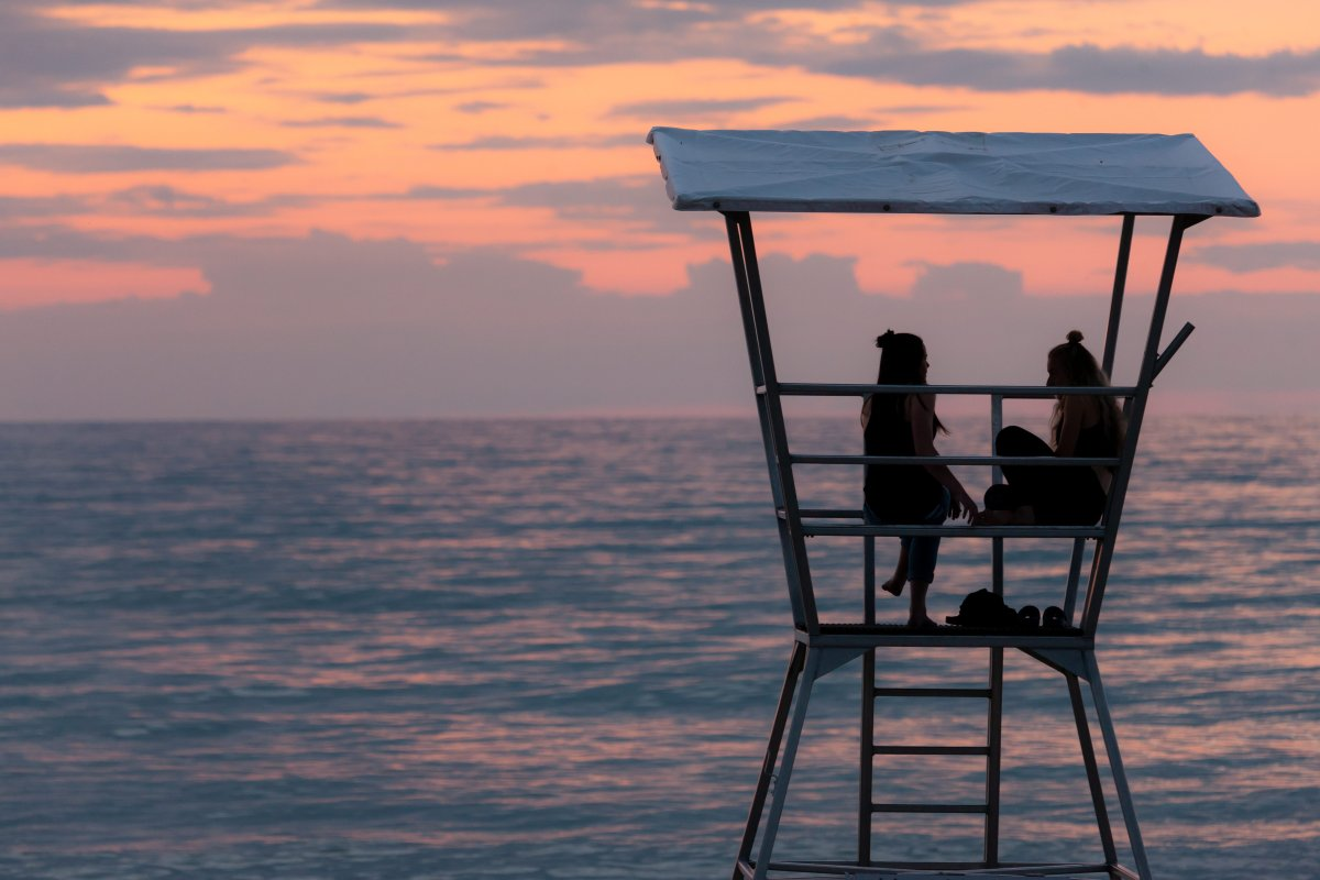 Two young women sit and talk in a lifeguard tower in Grand Bend, Ontario on July 28, 2018.