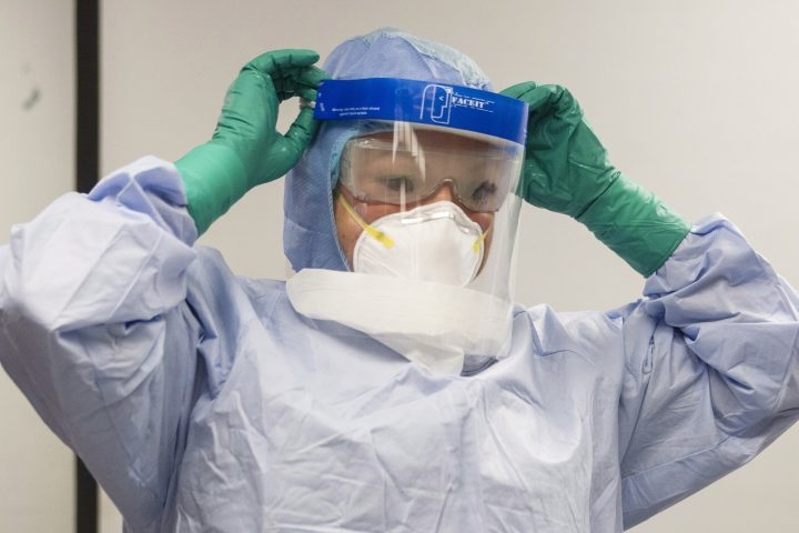 In this file photo, a healthcare professional adjusts her mask during a demonstration of Personal Protective Equipment (PPE) procedures. All employees of the Saint-Eustache hospital in the Laurentians region of Quebec are being tested for COVID-19 after an outbreak at the facility. Friday, July 31, 2020.