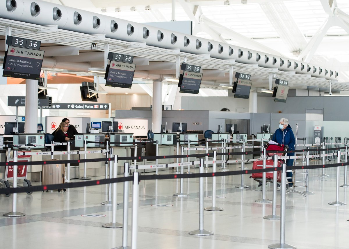 A lone lady walks in an empty Air Canada line at Pearson International Airport in Toronto on Wednesday, April 8, 2020. Health officials and the government have asked that people stay inside to help curb the spread of the coronavirus also known as COVID-19. THE CANADIAN PRESS/Nathan Denette.
