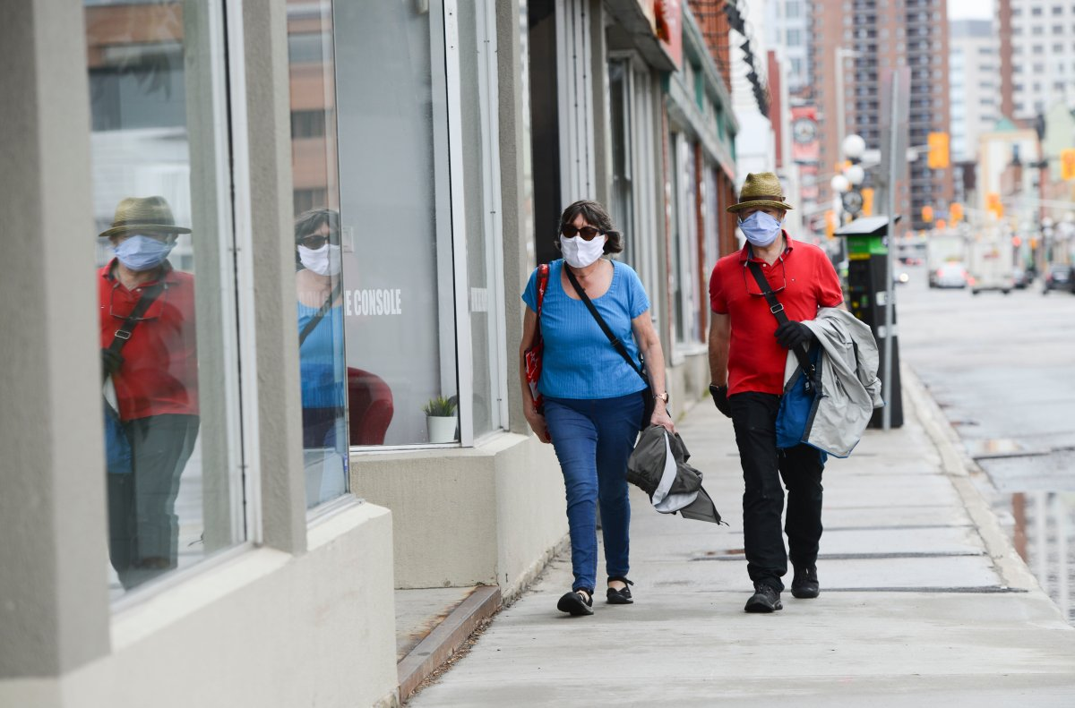 A couple wear masks while out for a walk in downtown Ottawa during the COVID-19 pandemic on Friday, May 1, 2020.