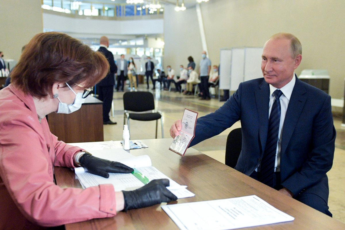 Russian President Vladimir Putin shows his passport to a member of an election commission as he arrives to take part in voting at a polling station in Moscow, Russia, Wednesday, July 1, 2020.
