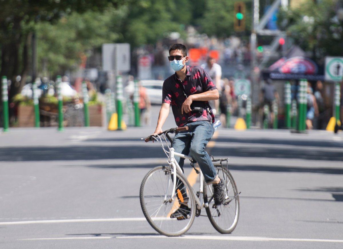 A man wears a face mask as he cycles on a street on Canada Day in Montreal, Wednesday, July 1, 2020, as the COVID-19 pandemic continues in Canada and around the world.