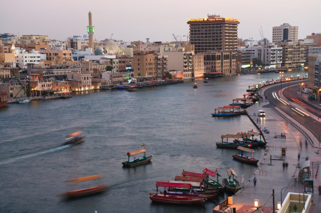 In this photograph taken with a slow shutter speed, traditional abra boats navigate the Dubai Creek in Dubai, United Arab Emirates, Wednesday, July 1, 2020.