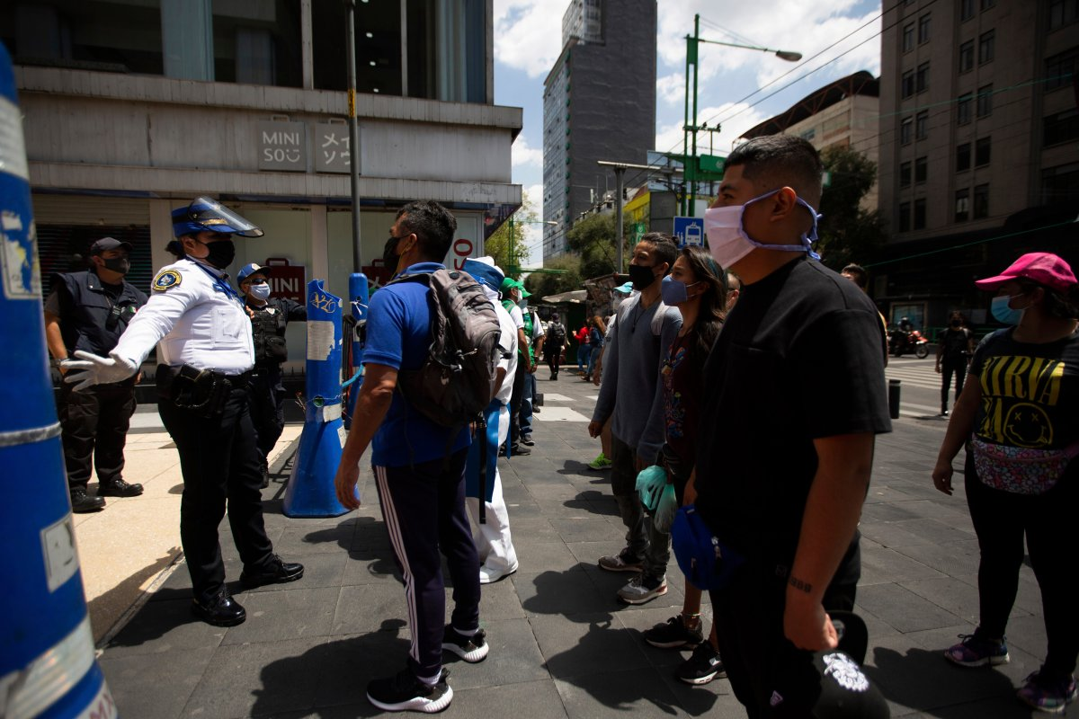 A Mexican police officer gives social-distancing and precautionary COVID-19 related guidelines to tourists in the historic center of Mexico City, Friday, July 3, 2020.