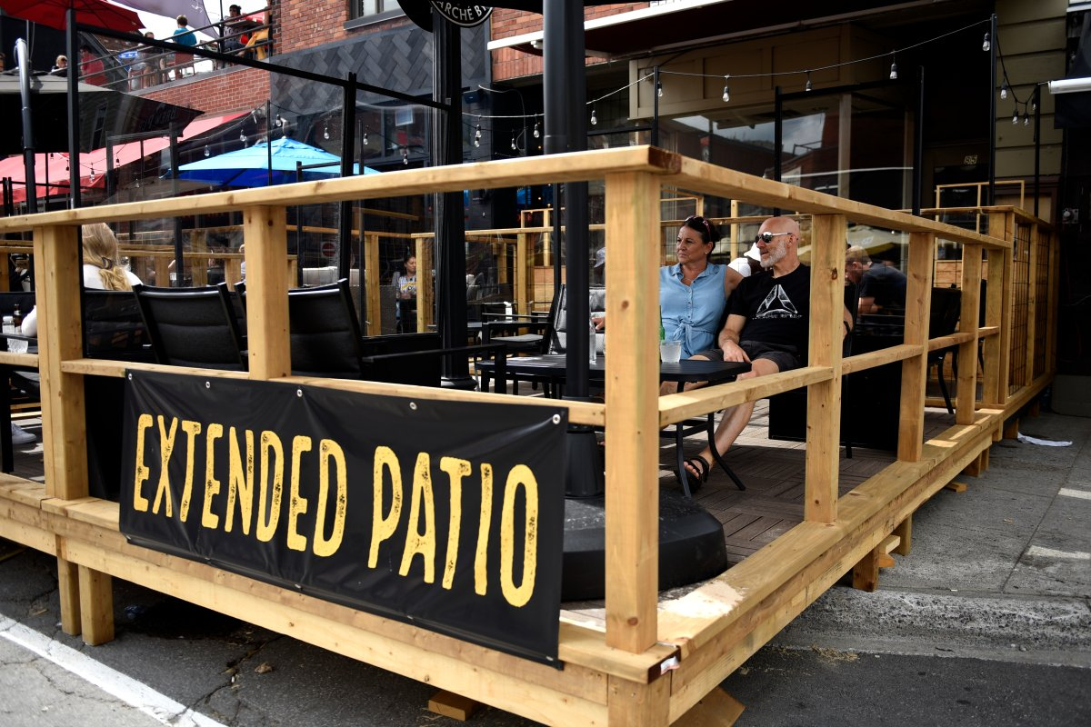 People sit on a bar's patio built on top of the sidewalk and street parking spaces in the Byward Market in Ottawa, on Sunday, July 12, 2020, in the midst of the COVID-19 pandemic.