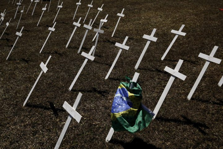 Rows of crosses representing the thousands of deaths due to the new coronavirus are displayed on a lawn during a protest demanding President Jair Bolsonaro be impeached, in front of the National Congress in Brasilia, Brazil, Tuesday, July 14, 2020.