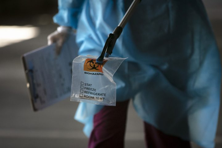 FILE - A physician assistant carries a nasal swab sample using a grabber at a COVID-19 drive-through testing site set up at the Anaheim Convention Center in Anaheim, Calif., Thursday, July 16, 2020.