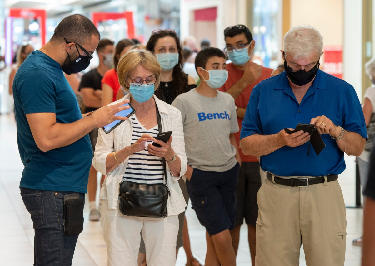 Shoppers wear masks as they line up at a mall on the third day of Quebec's mandatory mask order for all indoor public spaces 20, 2020 in Laval, Que.