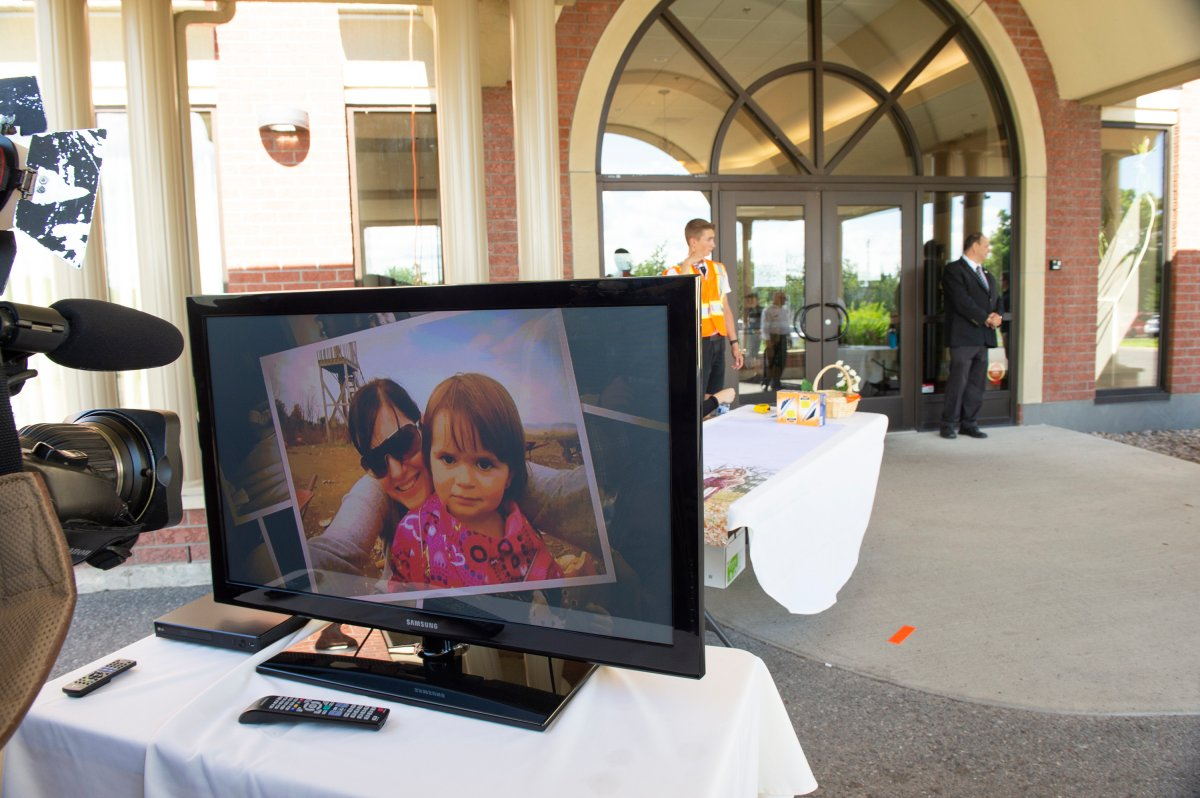A slideshow is shown outside the funeral home in Levis, Que., where the funerals of Romy and Norah Carpentier will be held on Monday, July 20, 2020.