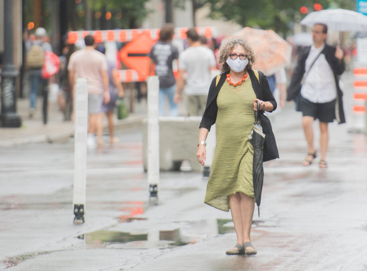 A woman wears a face mask as she walks along a street in Montreal, Saturday, July 11, 2020, as the COVID-19 pandemic continues in Canada and around the world.
