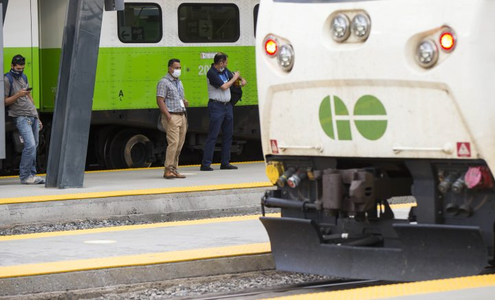 Passengers wearing face masks wait for a GO train on the platform at Union Station in Toronto on July 21, 2020.