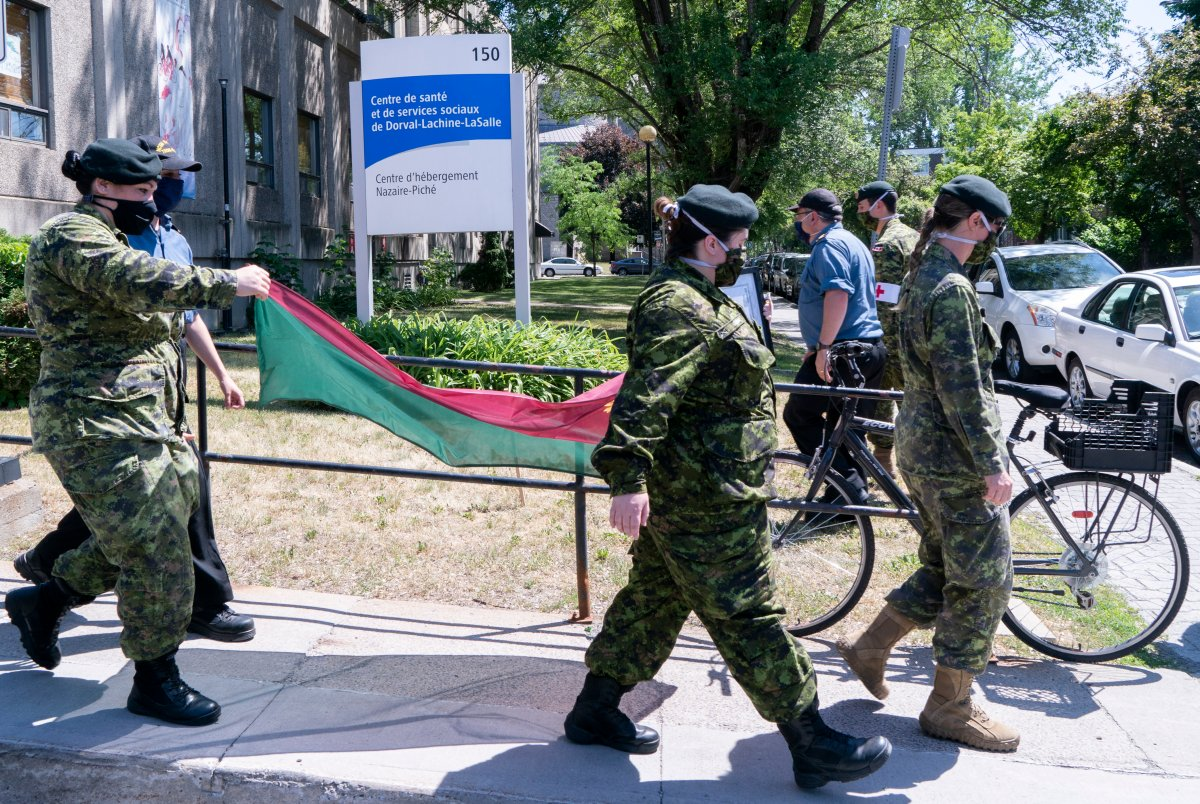 Soldiers walk away with the battalion flag following a ceremony marking the last day of military presence at the CHSLD Nazaire-Piche in Montreal, on June 17, 2020.
