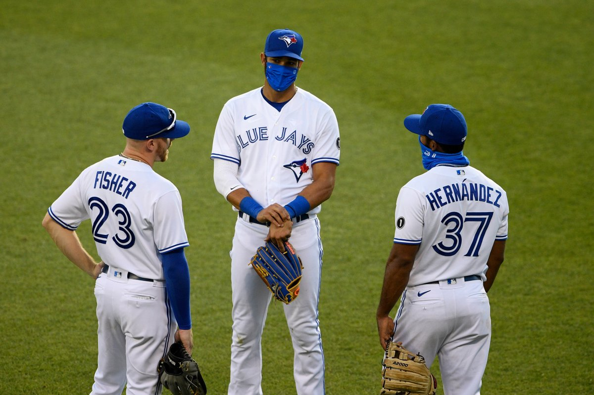 Toronto Blue Jays outfielders Derek Fisher (23), Lourdes Gurriel Jr., center, and Teoscar Hernandez (37) talk during a pitching change during the seventh inning of a baseball game against the Washington Nationals, Wednesday, July 29, 2020, in Washington.
