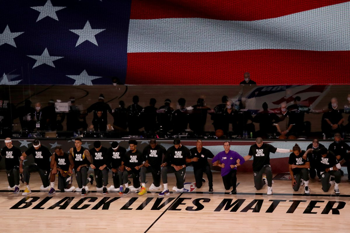 The Los Angeles Lakers and the Los Angeles Clippers wear Black Lives Matter shirts and kneel during the national anthem prior to an NBA basketball game Thursday, July 30, 2020, in Lake Buena Vista, Fla.