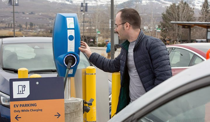 Majid Moradzadeh, a doctoral student in power engineering, inspects an electric vehicle charging station at UBC Okanagan.