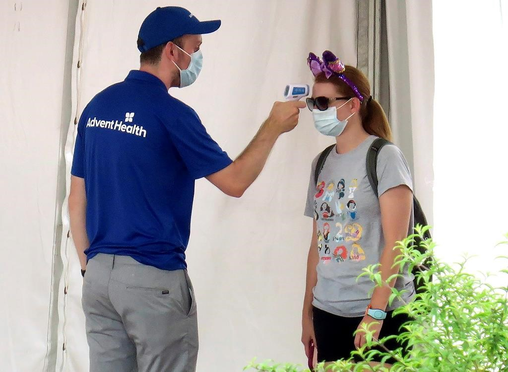 A guests gets her temperature taken before entering the official reopening day of the Magic Kingdom at Walt Disney World in Lake Buena Vista, Fla., Saturday, July 11, 2020. Disney reopened two Florida parks, the Magic Kingdom and Animal Kingdom, Saturday with limited capacity and safety protocols in place in response to the coronavirus pandemic. (Joe Burbank/Orlando Sentinel via AP).