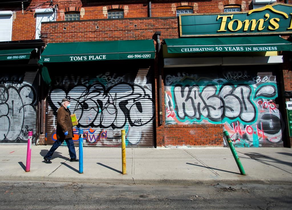 Small businesses are boarded up along an empty street in Kensington Market in Toronto amid COVID-19 lockdowns.