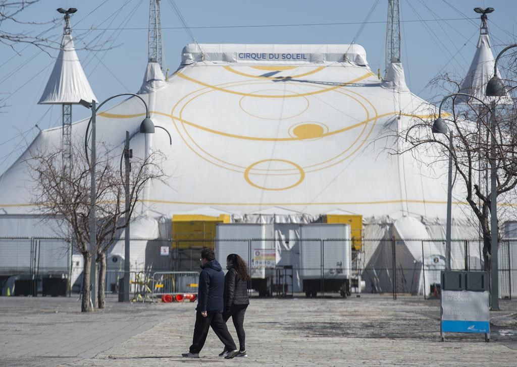 A man and woman walk by the Cirque du Soleil Big Top in Montreal's Old Port, Saturday, March 21, 2020.