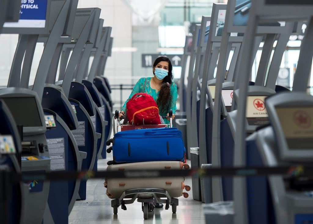 """A traveler walks between check-in kiosks at Toronto's Pearson International Airport for a """"Healthy Airport"""" during the COVID-19 pandemic in Toronto on Tuesday, June 23, 2020. THE CANADIAN PRESS/Nathan Denette."""