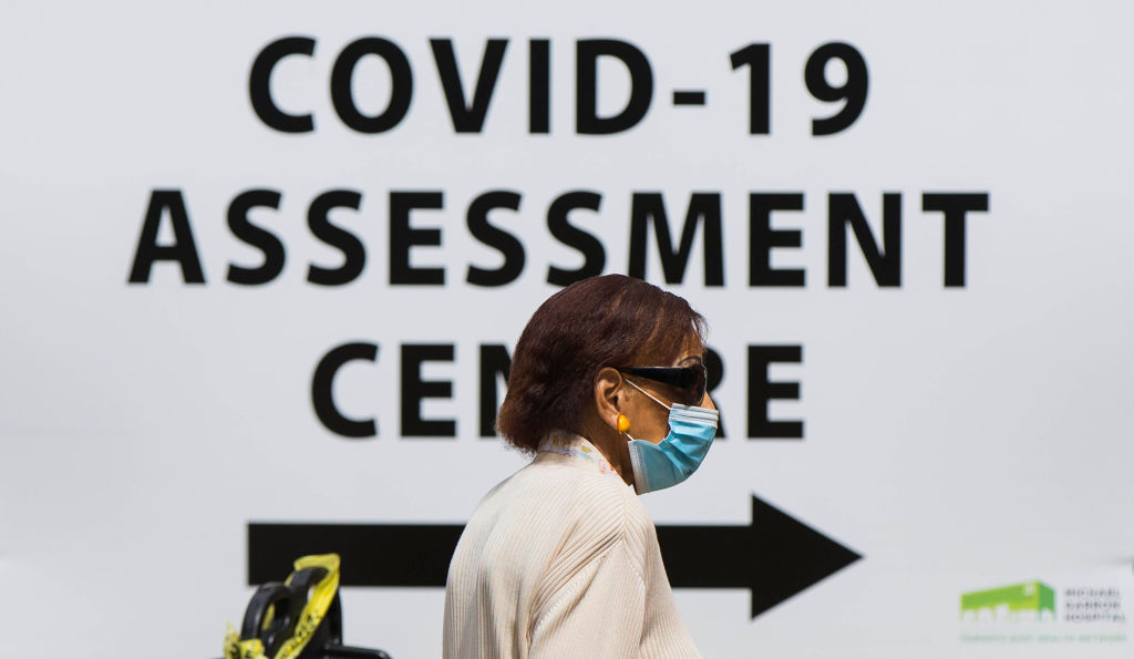 FILE - A woman wearing a face mask arrives at the COVID-19 assessment center of a hospital in Toronto, Canada, July 20, 2020.