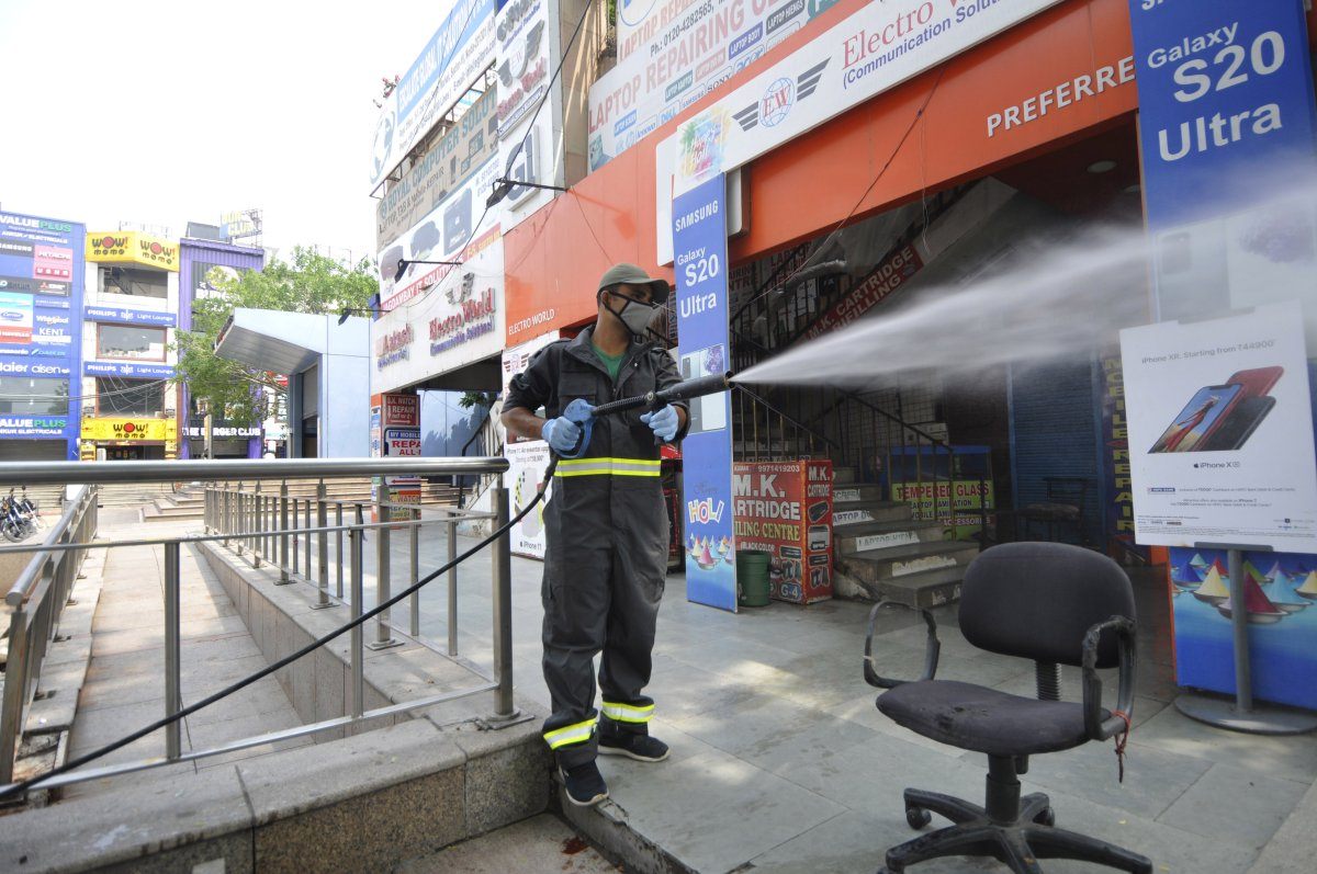NOIDA, INDIA - AUGUST 1: A fire brigade personnel chemically disinfects the mobile market premises, at Sector 18 during the weekend lockdown imposed by the state government, on August 1, 2020 in Noida, India.