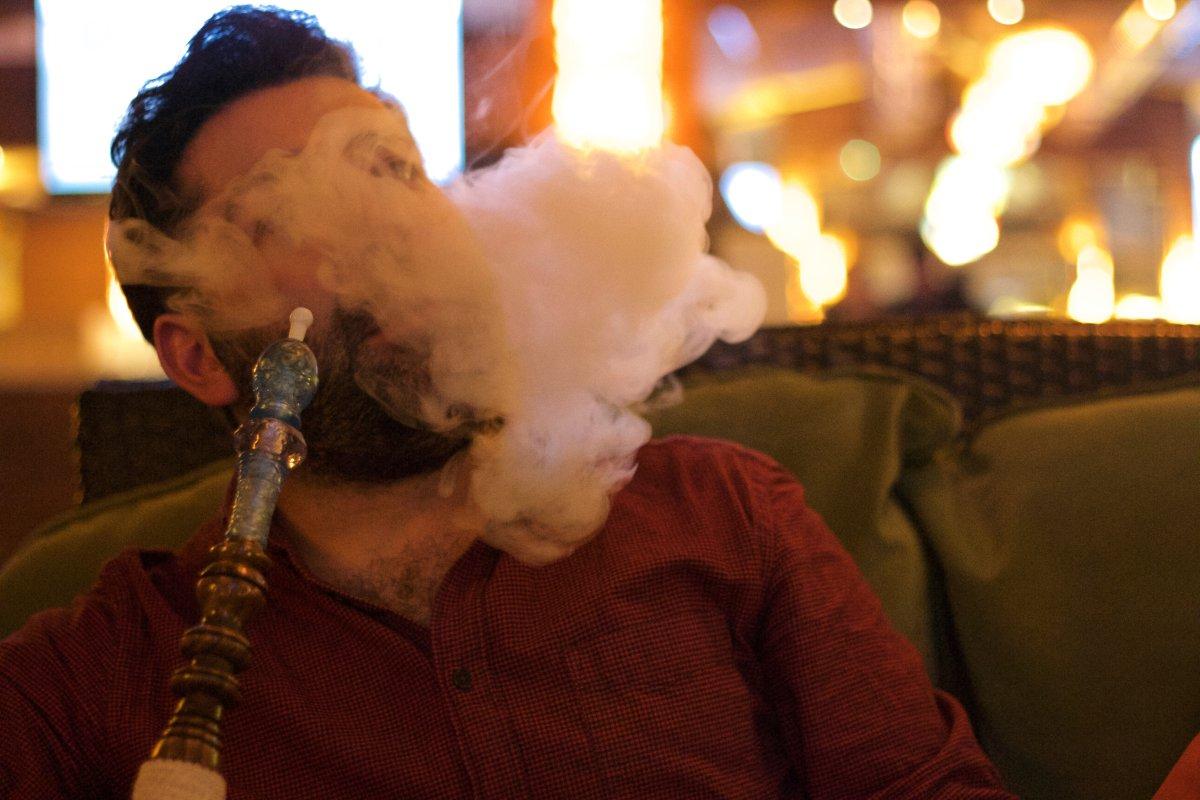 A stock image of a person smoking shisha.