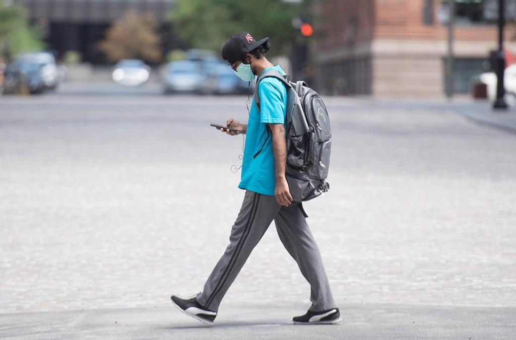 A man wears a face mask as he walks along a street in Montreal, Sunday, July 26, 2020, as the COVID-19 pandemic continues in Canada and around the world. THE CANADIAN PRESS/Graham Hughes.