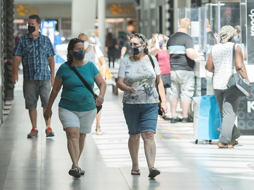 People wear face masks as they walk through a shopping mall in Montreal, Saturday, July 18, 2020, as the COVID-19 pandemic continues in Canada and around the world. The wearing of masks or protective face coverings is mandatory in Quebec as of today. THE CANADIAN PRESS/Graham Hughes.